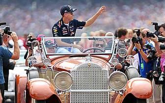Vor dem Start werden die Fahrer in Oldtimern auf die Strecke gefahren. Sebastian Vettel winkt den Fans. Im Rennen geht es ganz sicher schneller zu