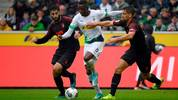 Moenchengladbach's Swiss midfielder Denis Zakaria (C) vies for the ball with Augsburg's German midfielder Rani Khedira (R) during the German first division Bundesliga football match Borussia Moenchengladbach vs FC Augsburg in Moenchengladbach, western Germany, on October 6, 2019. (Photo by Ina FASSBENDER / AFP) / DFL REGULATIONS PROHIBIT ANY USE OF PHOTOGRAPHS AS IMAGE SEQUENCES AND/OR QUASI-VIDEO (Photo by INA FASSBENDER/AFP via Getty Images)