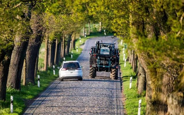 Landwirtschaftliche Fahrzeuge können Erntereste und rutschigen Dreck auf der Fahrbahn hinterlassen.