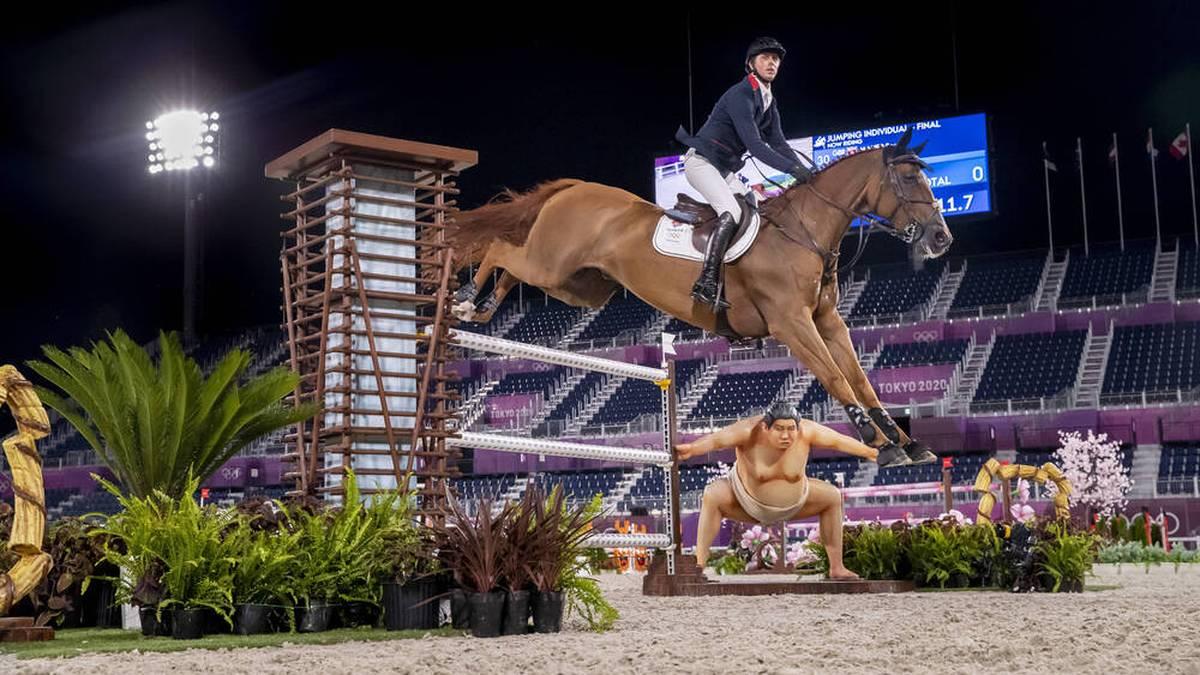 Der Sumoringer schaut sich die Landung der Pferde ganz genau an