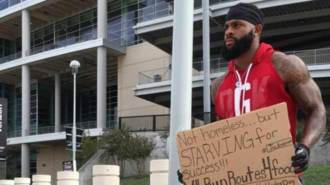 Joe Anderson steht mit seinem Schild vor dem Stadion in Houston