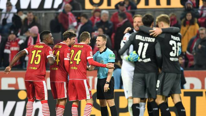COLOGNE, GERMANY - NOVEMBER 08: 1. FC Koeln players confront referee Robert Kampka after TSG 1899 Hoffenheim score their team's second goal, a penalty awarded to them following a VAR review during the Bundesliga match between 1. FC Koeln and TSG 1899 Hoffenheim at RheinEnergieStadion on November 08, 2019 in Cologne, Germany. (Photo by Jörg Schüler/Bongarts/Getty Images)