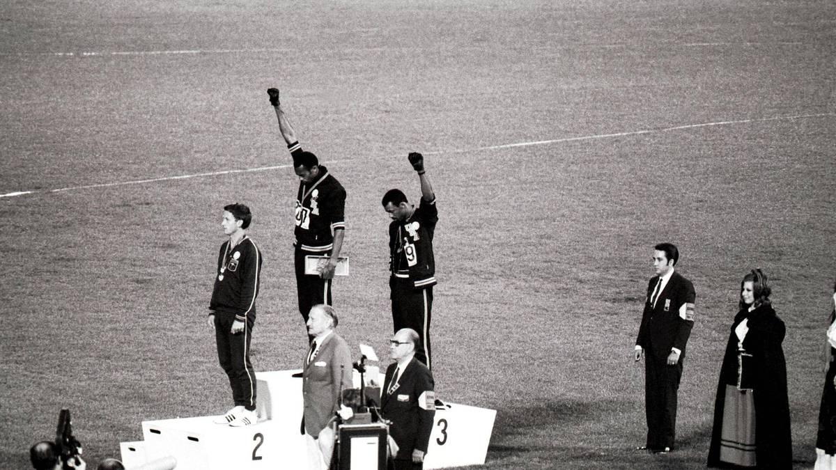 Tommie Smith (M.) und John Carlos reckten 1968 bei der Siegerehrung die Faust in die Höhe