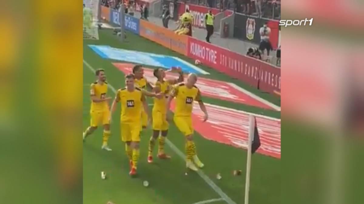 Nach dem Siegtor von Erling Haaland gegen Bayer Leverkusen wird die Dortmunder Jubeltraube mit Bierbechern beworfen. Jude Bellingham fängt ein Flugobjekt und trinkt daraus.