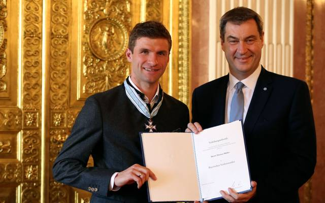 MUNICH, GERMANY - DECEMBER 03: Bavarian Prime Minister Markus Soeder (R) awards Thomas Mueller of FC Bayern Muenchen with the Bavarian Order Of Merit at Prinz-Carl-Palais on December 03, 2019 in Munich, Germany. (Photo by Alexander Hassenstein/Bongarts/Getty Images)