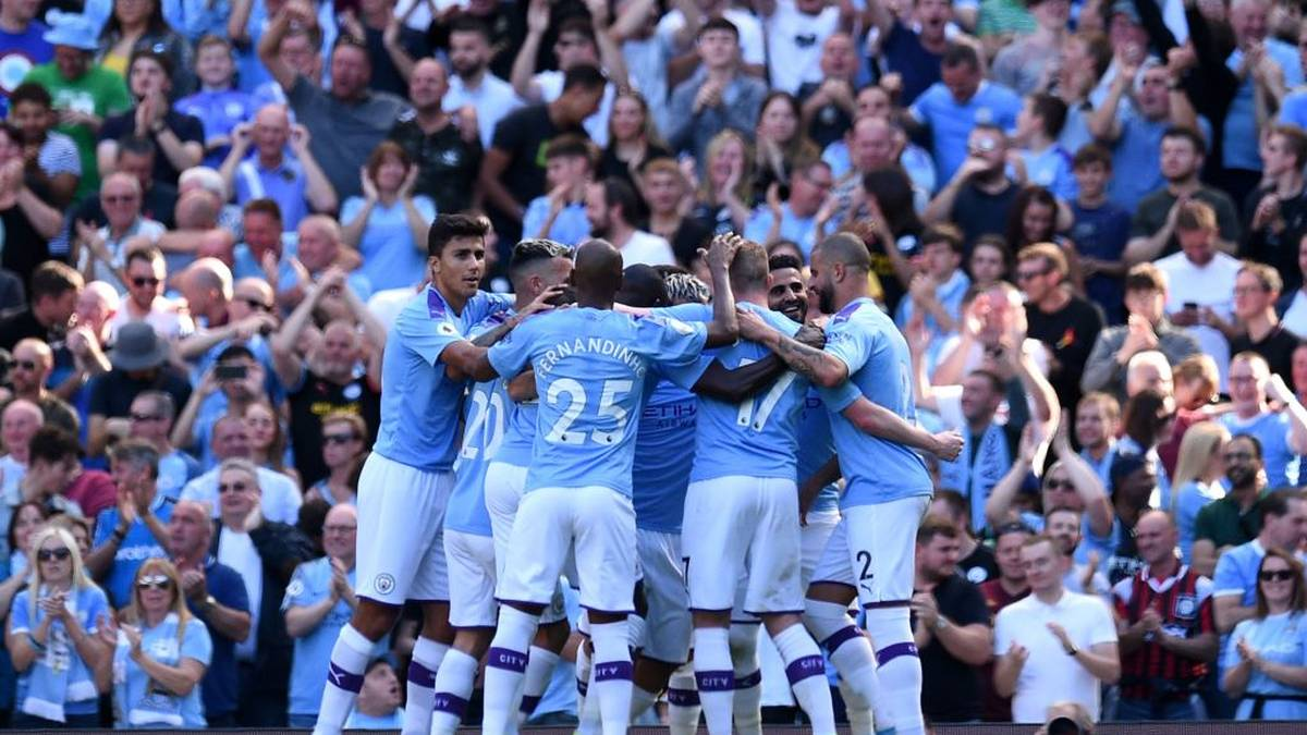 Manchester City's Algerian midfielder Riyad Mahrez celebrates with teammates after he scores his team's third goal during the English Premier League football match between Manchester City and Watford at the Etihad Stadium in Manchester, north west England, on September 21, 2019. (Photo by Oli SCARFF / AFP) / RESTRICTED TO EDITORIAL USE. No use with unauthorized audio, video, data, fixture lists, club/league logos or 'live' services. Online in-match use limited to 120 images. An additional 40 images may be used in extra time. No video emulation. Social media in-match use limited to 120 images. An additional 40 images may be used in extra time. No use in betting publications, games or single club/league/player publications. /         (Photo credit should read OLI SCARFF/AFP/Getty Images)