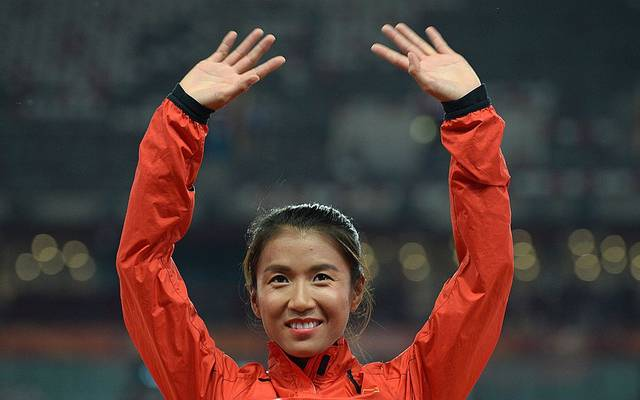 "China's gold medallist Liu Hong celebrates on the podium during the victory ceremony for the women's 20 kilometres race walk athletics event at the 2015 IAAF World Championships at the ""Bird's Nest"" National Stadium in Beijing on August 28, 2015.  AFP PHOTO / WANG ZHAO        (Photo credit should read WANG ZHAO/AFP/Getty Images)"