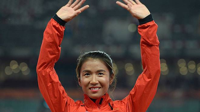 """China's gold medallist Liu Hong celebrates on the podium during the victory ceremony for the women's 20 kilometres race walk athletics event at the 2015 IAAF World Championships at the """"Bird's Nest"""" National Stadium in Beijing on August 28, 2015.  AFP PHOTO / WANG ZHAO        (Photo credit should read WANG ZHAO/AFP/Getty Images)"""