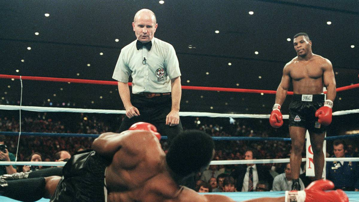 """Las Vegas, UNITED STATES:  (FILES) A file picture taken 22 November 1986 in Las Vegas shows Mike Tyson (R) during his fight against heavyweight champion Trevor Berbick to become the youngest heavyweight world champion in history. Twenty years after, the """"Baddest Man on the Planet"""" is aging as badly as any boxing cautionary tale.  AFP PHOTO  (Photo credit should read -/AFP via Getty Images)"""