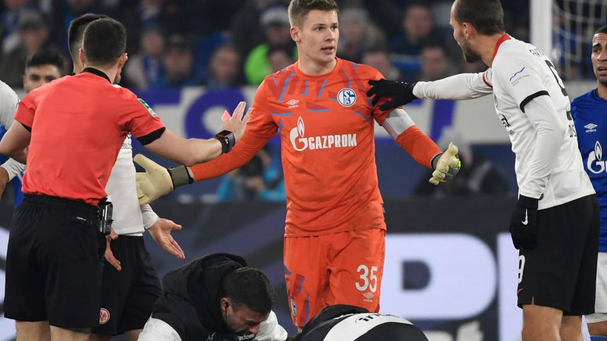 Schalke's German goalkeeper Alexander Nuebel (C) argues with Referee Felix Zwaye (L) and Frankfurt's Dutch forward Bas Dost after beeing shown a red card during the German first division Bundesliga football match Schalke 04 v Eintracht Frankfurt in Gelsenkirchen, on December 15, 2019. (Photo by INA FASSBENDER / AFP) / DFL REGULATIONS PROHIBIT ANY USE OF PHOTOGRAPHS AS IMAGE SEQUENCES AND/OR QUASI-VIDEO (Photo by INA FASSBENDER/AFP via Getty Images)