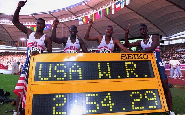 The U.S. 4x400m relay team, (L to R) Butch Reynolds, Andrew Valmon, Quincy Watts and Michael Johnson pose behind the score board after winning gold and setting a new world record with a time of 2:54.29 min at the Athletics World Championships in Stuttgart 22 August 1993. (Photo by Eric Feferberg / AFP)        (Photo credit should read ERIC FEFERBERG/AFP/Getty Images)