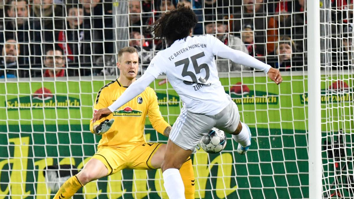 Munich's Zirkzee (R) scores the 2-1 past Freiburg's Dutch goalkeeper Mark Flekken during the German first division Bundesliga football match SC Freiburg v Bayern Munich, on December 18, 2019 in Freiburg. (Photo by THOMAS KIENZLE / AFP) / DFL REGULATIONS PROHIBIT ANY USE OF PHOTOGRAPHS AS IMAGE SEQUENCES AND/OR QUASI-VIDEO (Photo by THOMAS KIENZLE/AFP via Getty Images)