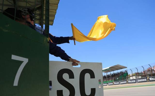 Safety Car Formel 1: Ein Race Marshall schwenkt die gelbe Flagge und signalisiert den Fahrern das Safety Car.