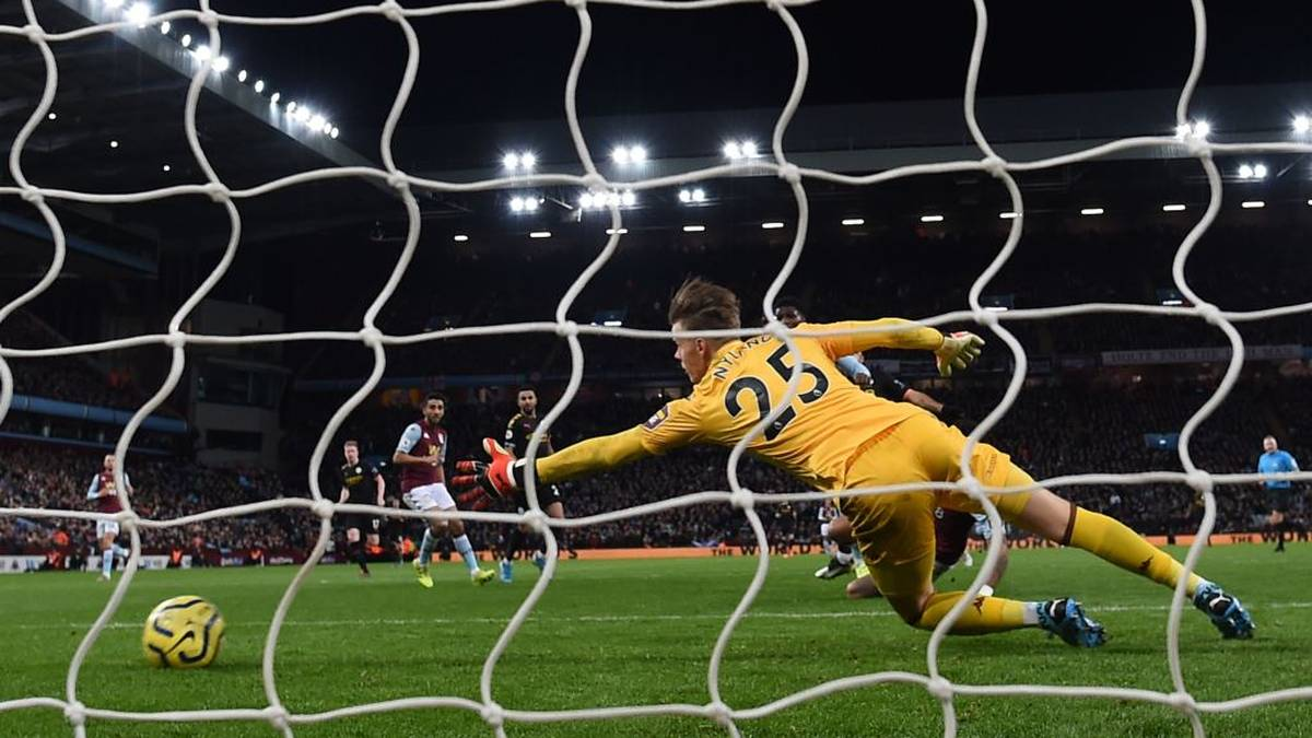 The ball beats Aston Villa's Norwegian goalkeeper Orjan Nyland (R) for Manchester City's Argentinian striker Sergio Aguero's second and City's fifth goal during the English Premier League football match between Aston Villa and Manchester City at Villa Park in Birmingham, central England on January 12, 2020. (Photo by PAUL ELLIS / AFP) / RESTRICTED TO EDITORIAL USE. No use with unauthorized audio, video, data, fixture lists, club/league logos or 'live' services. Online in-match use limited to 120 images. An additional 40 images may be used in extra time. No video emulation. Social media in-match use limited to 120 images. An additional 40 images may be used in extra time. No use in betting publications, games or single club/league/player publications. /  (Photo by PAUL ELLIS/AFP via Getty Images)