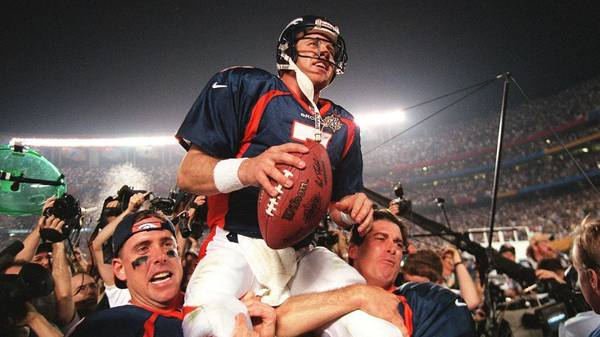 Denver Broncos quarterback John Elway (C) is carried by teammates Ed McCaffrey (L) and Bubby Brister (R) after the Broncos defeated the  Green Bay Packers 31-24 to win Super Bowl XXXII in San Diego, CA 25 January.       AFP PHOTO/Timothy A. CLARY (Photo by Timothy A. CLARY / AFP) (Photo by TIMOTHY A. CLARY/AFP via Getty Images)