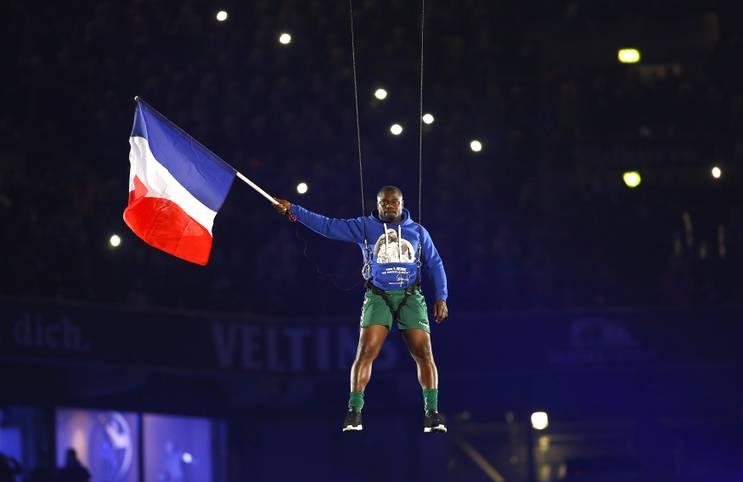 Große Gesten, große Emotionen: Das Abschiedsspiel von Gerald Asamoah auf Schalke steht noch ganz unter dem Eindruck der furchtbaren Terroranschläge von Paris. Asamoah zeigt seine Solidarität mit den Opfern und schwenkt die französische Fahne, während er an Stahlseilen durch die Arena schwebt