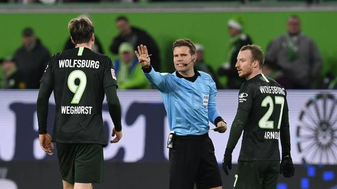 Wolfsburg's Dutch forward Wout Weghorst (L) and Wolfsburg's German midfielder Maximilian Arnold argue with the referee Felix Brych (C) during the German first division Bundesliga football match VfL Wolfsburg v Borussia Moenchengladbach in Wolfsburg, on December 15, 2019. (Photo by John MACDOUGALL / AFP) / DFL REGULATIONS PROHIBIT ANY USE OF PHOTOGRAPHS AS IMAGE SEQUENCES AND/OR QUASI-VIDEO (Photo by JOHN MACDOUGALL/AFP via Getty Images)