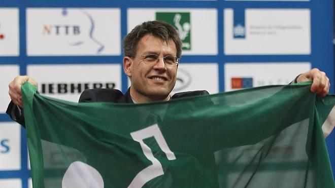 Thomas Weikert hält eine Fahne des ITTF in der Hand