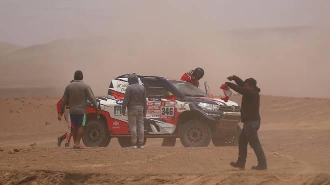 Andre Villas Boas und sein Beifahrer Ruben Faria steigen nach dem Crash an einer Wüsten-Düne wieder in ihr Fahrzeug ein