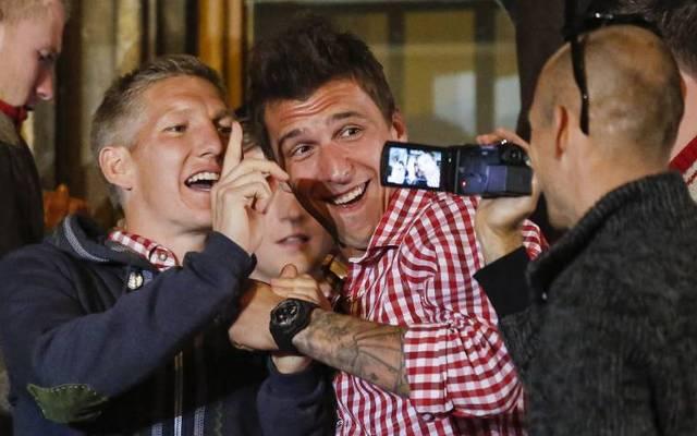 Arjen Robben (r.) filmt Bastian Schweinsteiger und Mario Mandzukic auf der Meisterfeier des FC Bayern