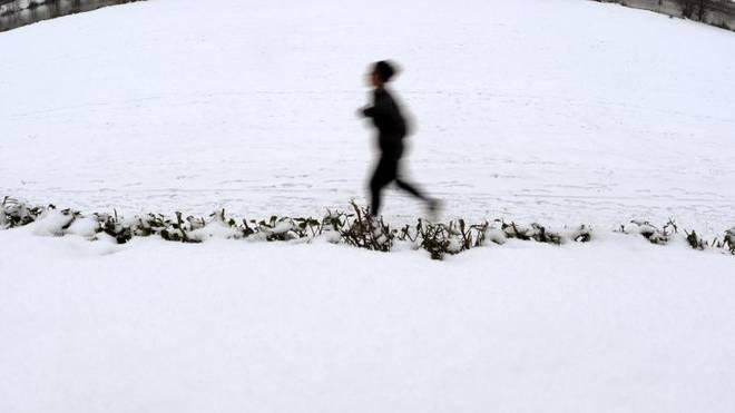 Eine Joggerin läuft an der mit Schnee bedeckten Neckarpromenade in Heidelberg entlang
