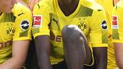 Dortmund's French midfielder Ousmane Dembele (C) smiles as he has taken seat for the team photo during a press event of German first division Bundesliga football club Borussia Dortmund on August 9, 2017 in Dortmund, western Germany. / AFP PHOTO / PATRIK STOLLARZ        (Photo credit should read PATRIK STOLLARZ/AFP/Getty Images)