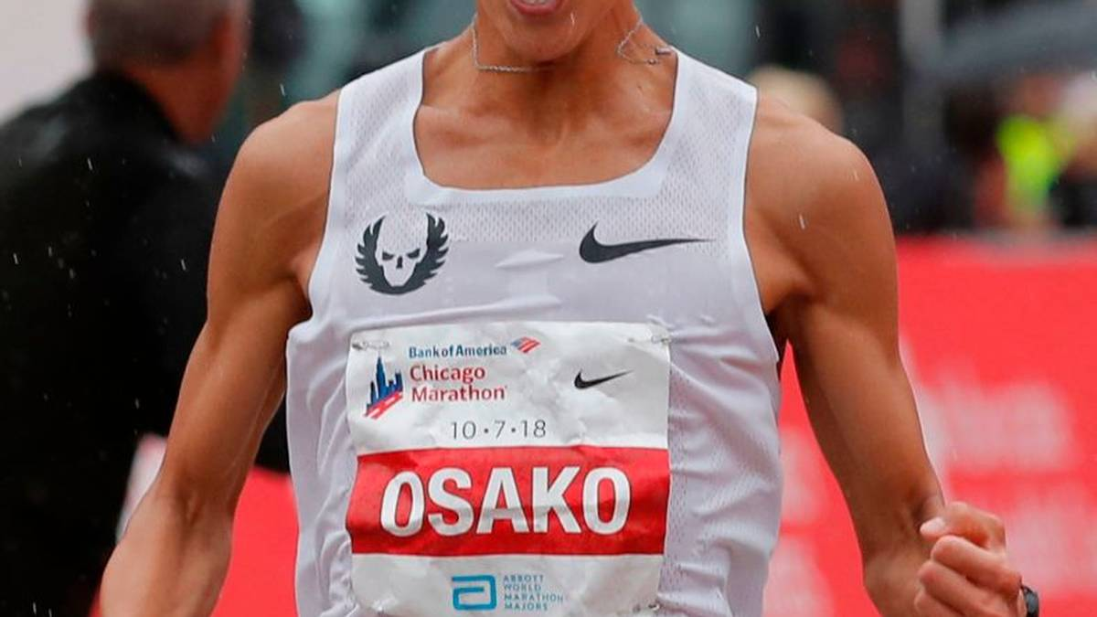 Suguru Osako of Japan reacts after finishing third in the Chicago Marathon in Chicago, on October 7, 2018. - British athletics star Mo Farah won the Chicago Marathon men's title on Sunday in an unofficial time of 2hr 5min 11sec, shattering a European record with a spectacular finishing surge. The world and Olympic 5,000 and 10,000-meter champion became the first British man to capture the event since Paul Evans in 1996.The 35-year-old Somalia-born Briton claimed the biggest victory since he turned his attention to the distance a year ago to defeat Ethiopia's Mosinet Geremew by 13 seconds with Japan's Suguru Osako third in 2:05:50. (Photo by JIM YOUNG / AFP) / The erroneous mention appearing in the metadata of this photo by JIM YOUNG has been modified in AFP systems in the following manner: [Suguru Osako of Japan] instead of [Suguru Osaka of Japan]. Please immediately remove the erroneous mention from all your online services and delete it from your servers. If you have been authorized by AFP to distribute it to third parties, please ensure that the same actions are carried out by them. Failure to promptly comply with these instructions will entail liability on your part for any continued or post notification usage. Therefore we thank you very much for all your attention and prompt action. We are sorry for the inconvenience this notification may cause and remain at your disposal for any further information you may require.        (Photo credit should read JIM YOUNG/AFP/Getty Images)