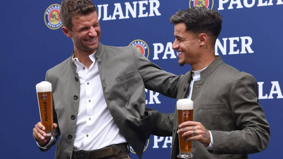 Bayern Munich's Brazilian midfielder Philippe Coutinho and teammate striker Thomas Mueller (L), wearing traditional Bavarian outfits, pose with beers during an advertising photo shooting on September 1, 2019 in Munich, southern Germany. (Photo by Christof STACHE / AFP)        (Photo credit should read CHRISTOF STACHE/AFP/Getty Images)
