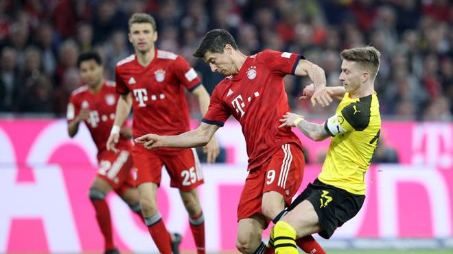 MUNICH, GERMANY - APRIL 06: Robert Lewandowski of Bayern Munich is challenged by Marco Reus of Borussia Dortmund during the Bundesliga match between FC Bayern Muenchen and Borussia Dortmund at Allianz Arena on April 06, 2019 in Munich, Germany. (Photo by Adam Pretty/Bongarts/Getty Images)