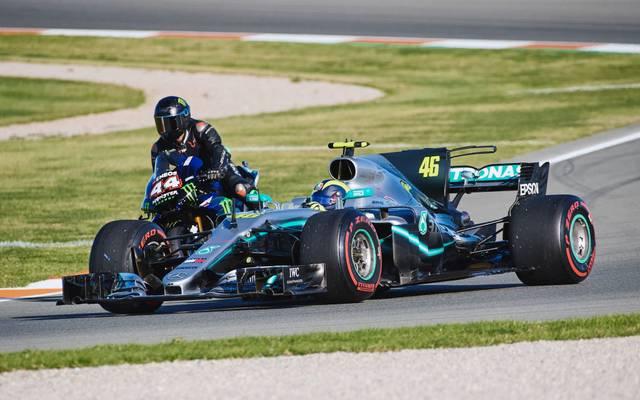 Lewis Hamilton (l.) versucht sich auf dem Motorrad, Valentino Rossi im Silberpfeil