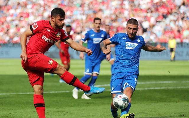 LEVERKUSEN, GERMANY - AUGUST 31: Kevin Volland of Bayer 04 Leverkusen shoots past Konstantinos Stafylidis of TSG 1899 Hoffenheim during the Bundesliga match between Bayer 04 Leverkusen and TSG 1899 Hoffenheim at BayArena on August 31, 2019 in Leverkusen, Germany. (Photo by Christof Koepsel/Bongarts/Getty Images)