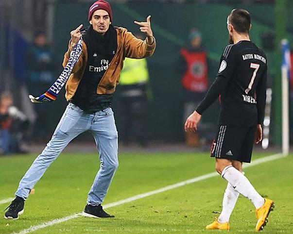 Im DFB-Pokal-Spiel zwischen dem HSV und dem FC Bayern sorgt ein Flitzer kurz vor Schluss für Aufregung. Mit seinem Schal schlägt er Franck Ribery und zeigt ihm anschließend den doppelten Stinkefinger. Doch nicht überall zeigen sich Flitzer von ihrer unsportlichen Seite. SPORT1 zeigt Flitzer aus der ganzen Welt des Sports