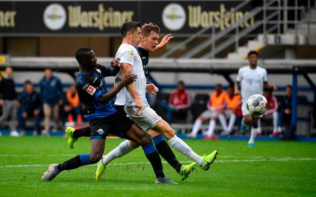 Munich's Polish forward Robert Lewandowski (C) scores the 1-3 goal during the German First division Bundesliga football match between SC Paderborn and Bayern Munich in Paderborn, on September 28, 2019. (Photo by INA FASSBENDER / AFP) / DFL REGULATIONS PROHIBIT ANY USE OF PHOTOGRAPHS AS IMAGE SEQUENCES AND/OR QUASI-VIDEO        (Photo credit should read INA FASSBENDER/AFP via Getty Images)