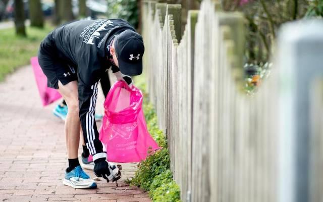 Ein Jogger sammelt Müll