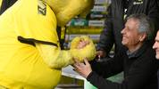 Mascot Emma shakes hands with Dortmund's Swiss coach Lucien Favre prior the German first division Bundesliga football match between Borussia Dortmund and VfL Wolfsburg on November 2, 2019 in Dortmund, western Germany. (Photo by INA FASSBENDER / AFP) / DFL REGULATIONS PROHIBIT ANY USE OF PHOTOGRAPHS AS IMAGE SEQUENCES AND/OR QUASI-VIDEO (Photo by INA FASSBENDER/AFP via Getty Images)