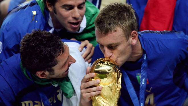 Berlin, GERMANY:  Italian defender Marco Materazzi (L) looks on as Italian midfielder Daniele De Rossi (R) kisses the World Cup trophy following their victory in the World Cup 2006 final football match between Italy and France at Berlin's Olympic Stadium, 09 July 2006.  Italy won 5-4 in the penalty shootout after the teams finished in extra time 1-1.     AFP PHOTO / ODD ANDERSEN  (Photo credit should read ODD ANDERSEN/AFP via Getty Images)