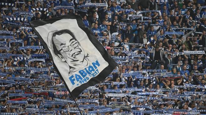 Eine große Fahne mit dem Bild des verstorbenen Fans wird im Schalker Fanblock geschwenkt