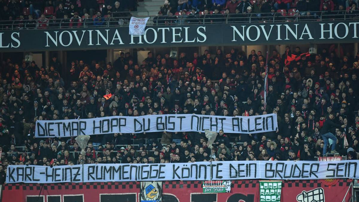 """NUREMBERG, GERMANY - MARCH 06: Supporters of Nuernberg hold up a sign that reads """"Dietmar Hopp du bist nicht allein, Karl-Heinz Rummenigge könnte dein Bruder sein."""" (Dietmar Hopp you are not alone, Karl-Heinz Rummenigge could be your brother.) during the Second Bundesliga match between 1. FC Nürnberg and Hannover 96 at Max-Morlock-Stadion on March 06, 2020 in Nuremberg, Germany. (Photo by Sebastian Widmann/Bongarts/Getty Images)"""