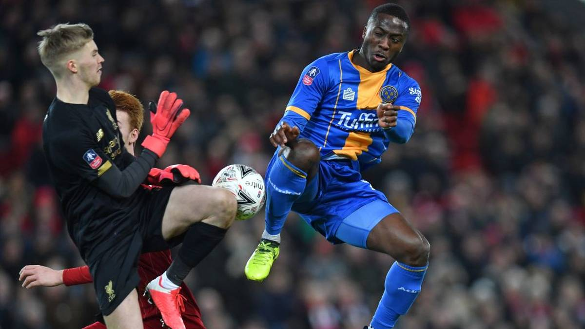 Shrewsbury Town's Nigerian striker Daniel Udoh (R) vies with Liverpool's Irish goalkeeper Caoimhin Kelleher (L) during the English FA Cup fourth round reply football match between Liverpool and Shrewsbury Town at Anfield in Liverpool, north west England on February 4, 2020. (Photo by Paul ELLIS / AFP) / RESTRICTED TO EDITORIAL USE. No use with unauthorized audio, video, data, fixture lists, club/league logos or 'live' services. Online in-match use limited to 120 images. An additional 40 images may be used in extra time. No video emulation. Social media in-match use limited to 120 images. An additional 40 images may be used in extra time. No use in betting publications, games or single club/league/player publications. /  (Photo by PAUL ELLIS/AFP via Getty Images)