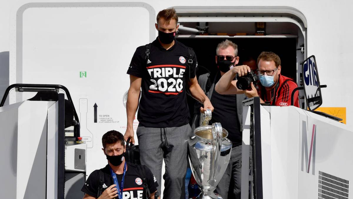 MUNICH, GERMANY - AUGUST 24: Manuel Neuer (C) of FC Bayern Muenchen carries the trophy as UEFA Champions League winners FC Bayern Munich arrive at Airport Munich on August 24, 2020 in Munich, Germany. (Photo by Philipp Guelland - Pool/Getty Images)
