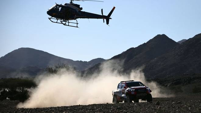 TOPSHOT - A helicopter flies as Toyota's driver Fernando Alonso of Spain and co-driver Marc Coma of Spain compete during the Stage 2 of the Dakar 2020 between Al Wajh and Neom, Saudi Arabia, on January 6, 2020. (Photo by FRANCK FIFE / AFP) (Photo by FRANCK FIFE/AFP via Getty Images)