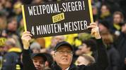"DORTMUND, GERMANY - NOVEMBER 25: A Dortmund supporter holds up a sign that reads: ""World Cup Winner against 4 min Champion"" before the Bundesliga match between Borussia Dortmund and FC Schalke 04 at Signal Iduna Park on November 25, 2017 in Dortmund, Germany. (Photo by Christof Koepsel/Bongarts/Getty Images)"