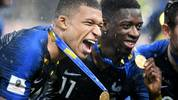 TOPSHOT - France's forward Kylian Mbappe (L) and France's forward Ousmane Dembele celebrate with their medals after the Russia 2018 World Cup final football match between France and Croatia at the Luzhniki Stadium in Moscow on July 15, 2018. - France won the World Cup for the second time in their history after beating Croatia 4-2 in the final in Moscow's Luzhniki Stadium on Sunday. (Photo by Jewel SAMAD / AFP) / RESTRICTED TO EDITORIAL USE - NO MOBILE PUSH ALERTS/DOWNLOADS        (Photo credit should read JEWEL SAMAD/AFP/Getty Images)