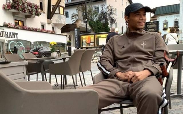 Leroy Sané sitzt im braunen Trainingsanzug lächelnd vor einem Restaurant