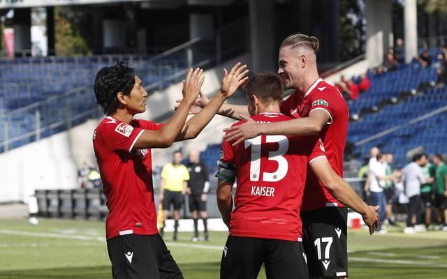 Hannovers Genki Haraguchi (l.), und Marvin Ducksch (r.) feiern mit Torschütze Dominik Kaiser