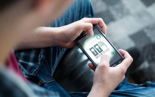 Ein Jugendlicher spielt in einem Wohnheim für computersüchtige Jugendliche mit einem Mobiltelefon.
