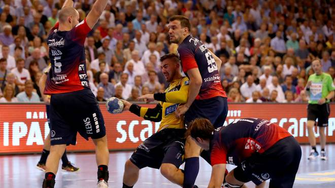 FLENSBURG, GERMANY - AUGUST 29: Simon Hald Jensen (L) of Flensburg-Handewitt challenges Jannik Kohlbacher of Rhein-Neckar Loewen during the Liqui Moly Handball Bundesliga match between SG Flensburg-Handewitt and Rhein-Neckar Loewen at Flens-Arena on August 29, 2019 in Flensburg, Germany. (Photo by Martin Rose/Bongarts/Getty Images)