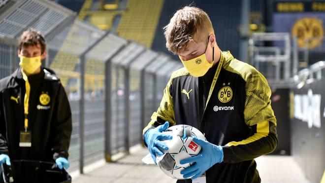 Der Balljunge der Partie Borussia Dortmund gegen Schalke 04 desinfiziert einen Spielball