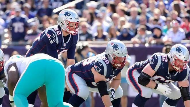 NFL Positionen: Der Quarterback (12) steht hinter der Offensive Line.