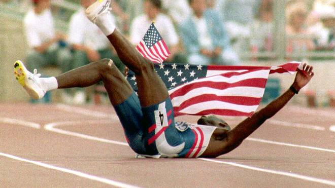 BARCELONA, SPAIN - AUGUST 6:  Kevin Young of the U.S. lies on the ground as he holds the American flag 06 August, 1992 in Barcelona shortly after winning the gold medal in the men's 400 meter hurdles with a world record setting time of 46.78 seconds.  (Photo credit should read MICHEL GANGNE/AFP/Getty Images)